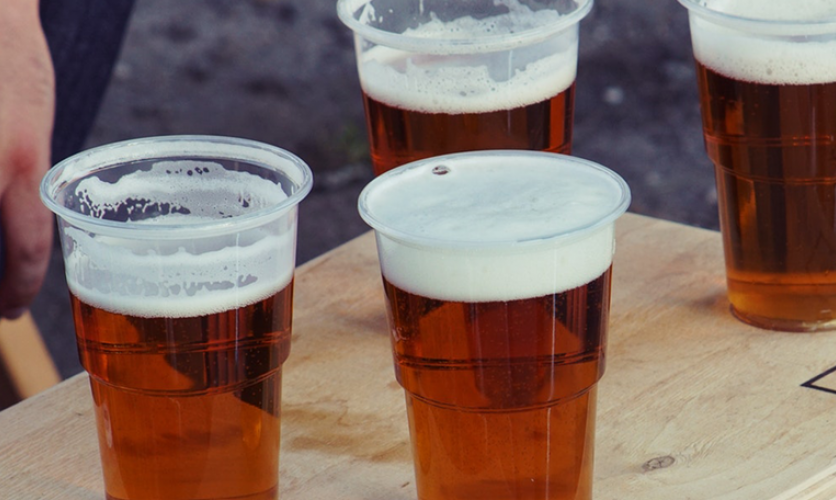 A group of clear plastic cups filled with beer.
