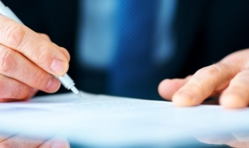 Hand holding a pen and signing a document.
