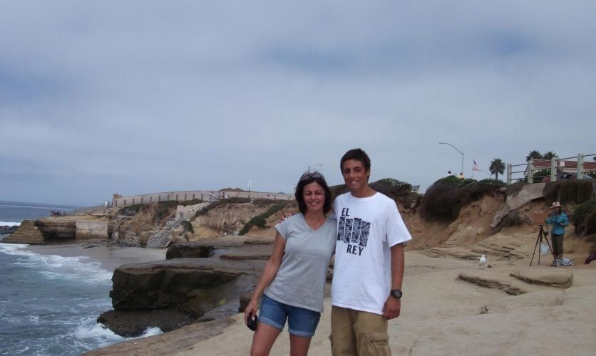 A man and women in shorts and tshirts standing next to the ocean.