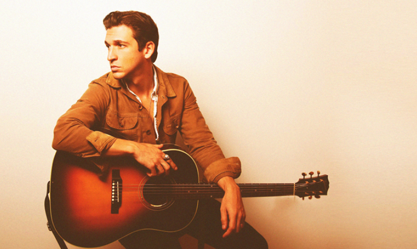 Man sitting with a guitar in his knee, looking off thoughtfully.
