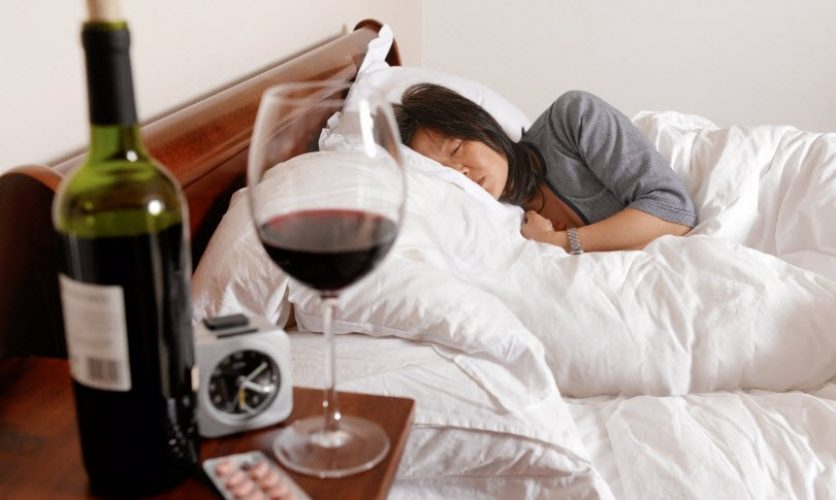 Woman lying in bed with a bottle, glass of wine, and pills on the nightstand.