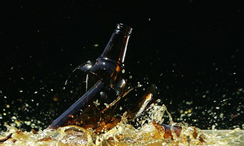 Broken beer bottle shattering on the floor.