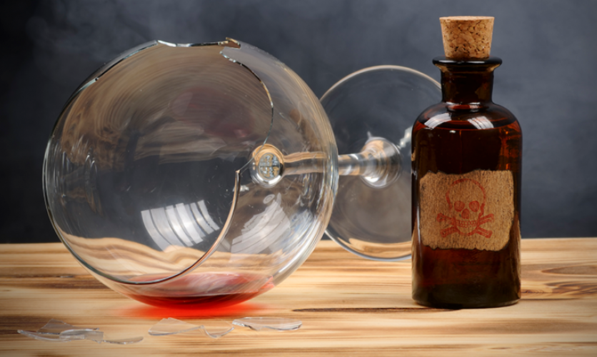 Broken wine glass on its side, next to a small apothecary bottle with a skull on the label.