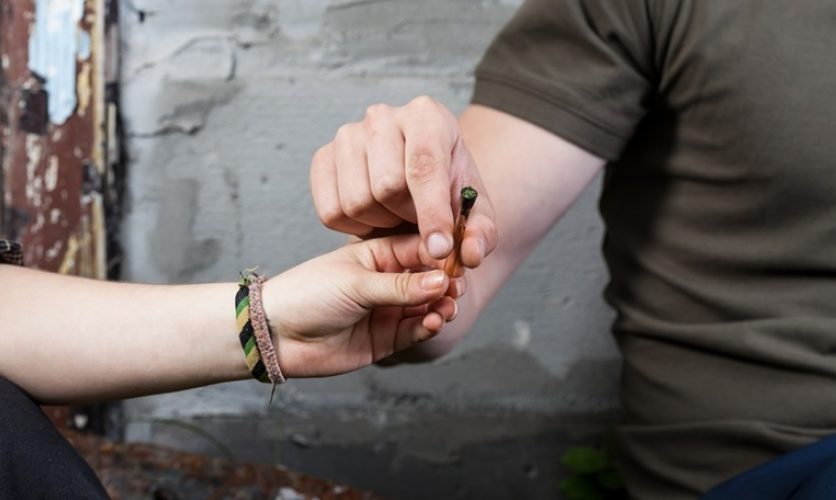 Close up of hands exchanging a blunt.