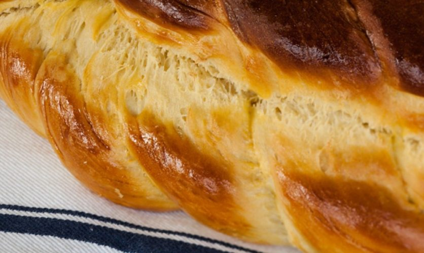 Close up image of a braided challah loaf on a tea towel.