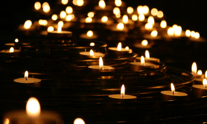 Many flames of votive candles lit in darkness.