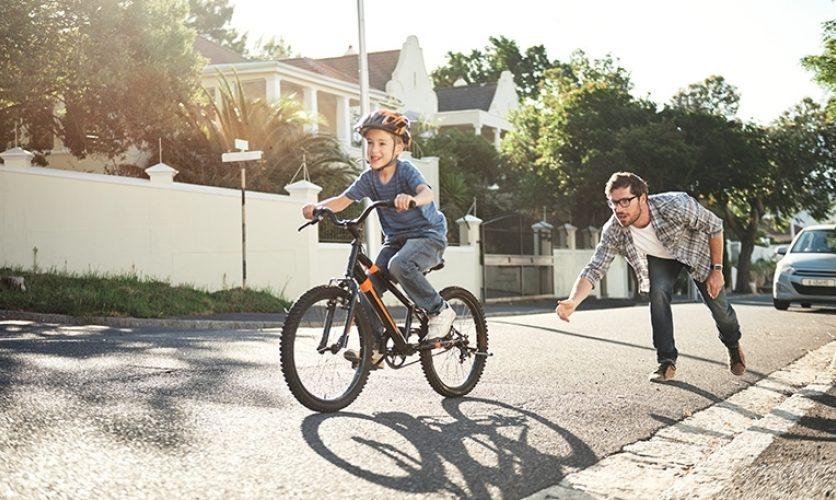 A man teaching a child to ride a bike on a suburban street.