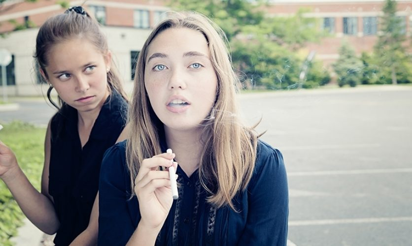 Two young women smoking in a parking lot, one blowing smoke out of her mouth.