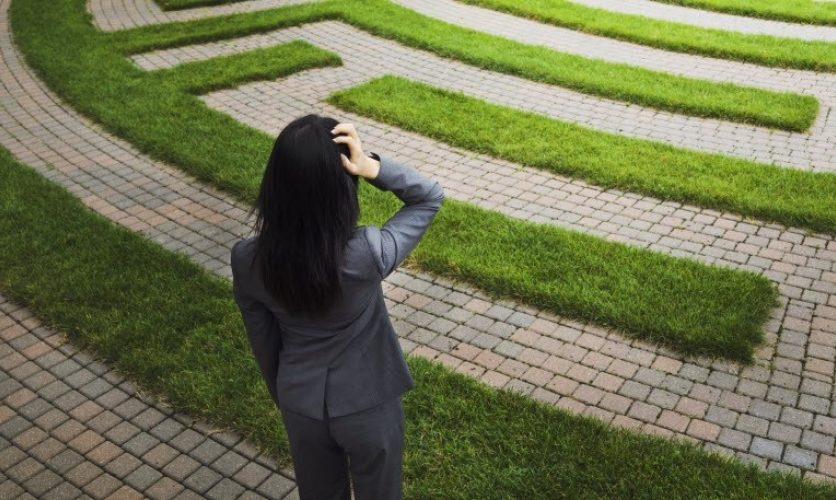 Confused looking woman gazing at a maze made of grass and shrubs.