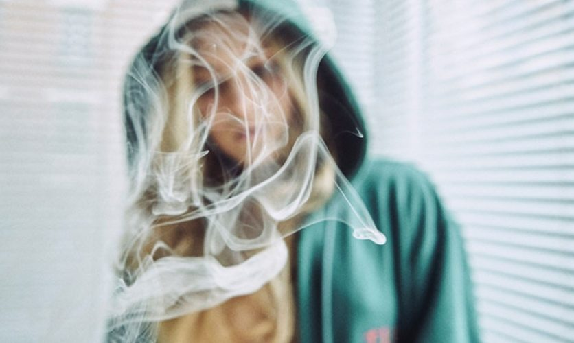 Out-of-focus person wearing a hoodie in the background with plumes of smoke in the foreground.