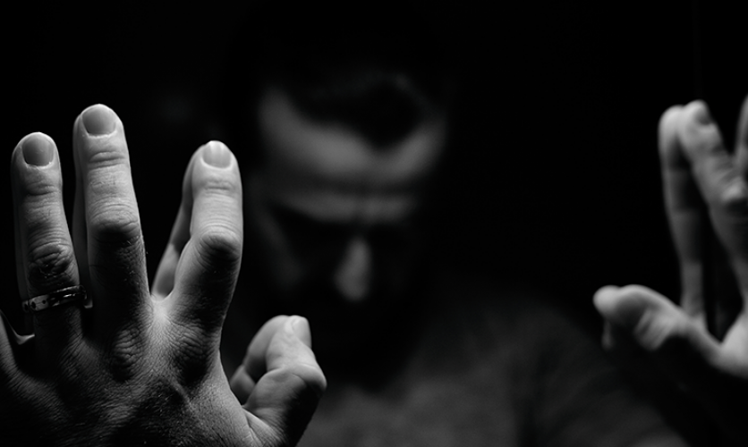 Black and white image of a somber person with their hands up against their reflection in the mirror.