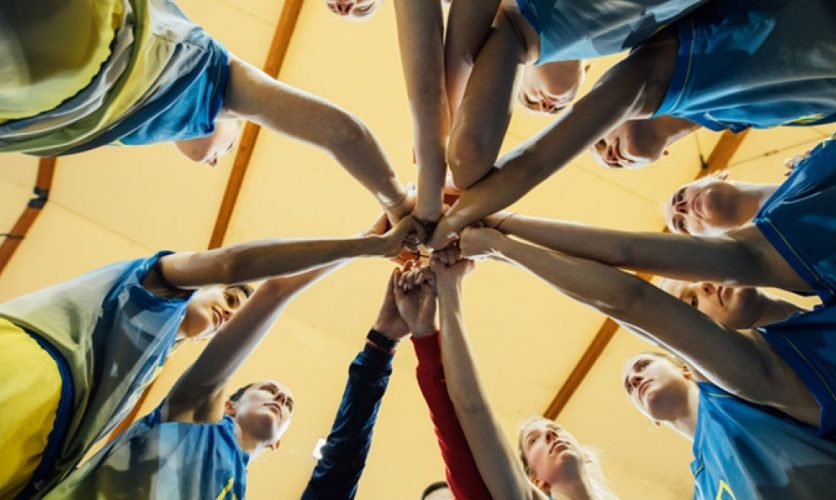 View from beneath a team standing in a circle with their hands together in the middle.