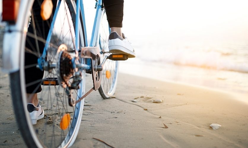 Close up of a person's feet on a bike at the beach.