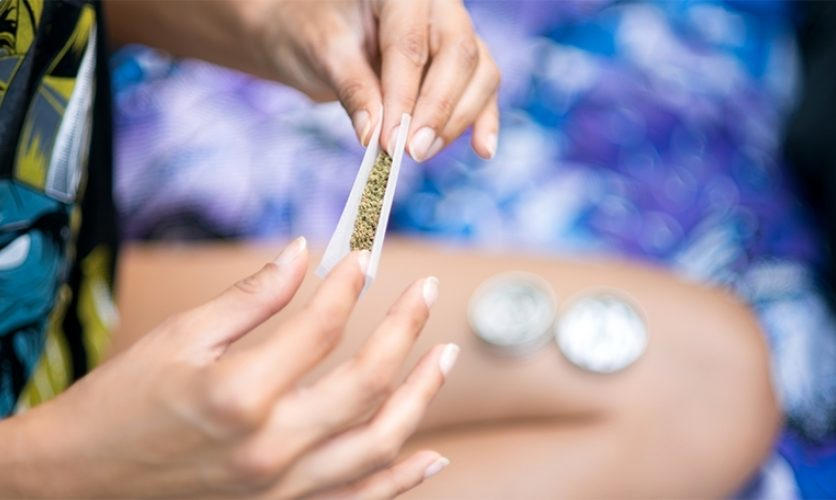 Close up of young person with manicured hands rolling a joint.