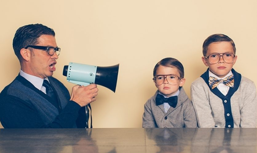 Man holding a megaphone shouting at two young, sad-looking children in bowties.