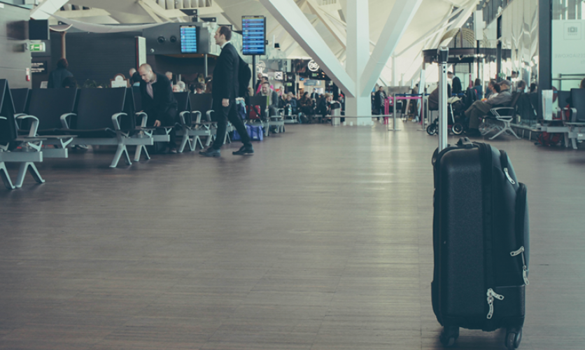 A view of an airport terminal with an unattended piece of luggage at the forefront.