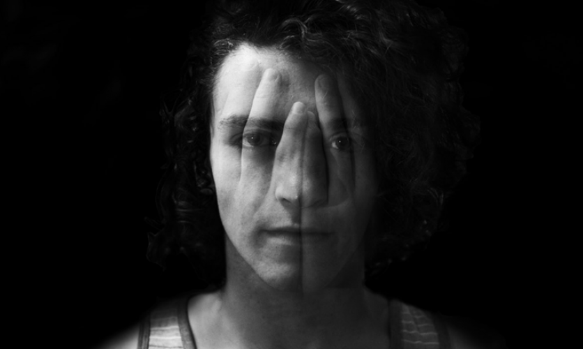 Black and white double exposure photo of young man with hands over his face.