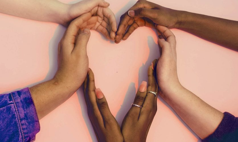 Several hands making the shape of a heart.