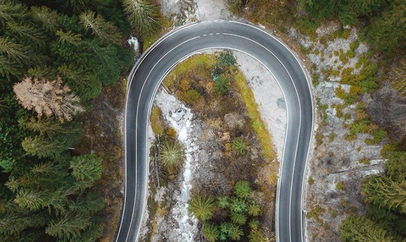 Aerial view of a curving road in the woods.