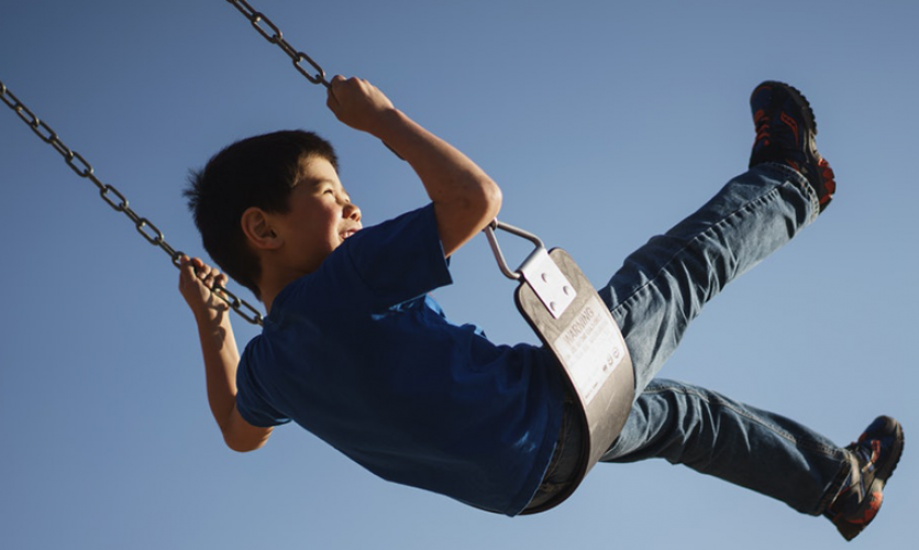 Young boy swinging on a swing and smiling.