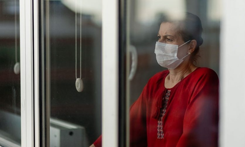 Woman wearing a surgical mask looks angrily out of window.