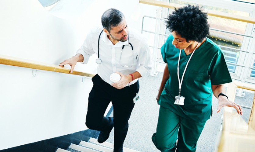 Doctor and nurse in conversation, ascending stairs.