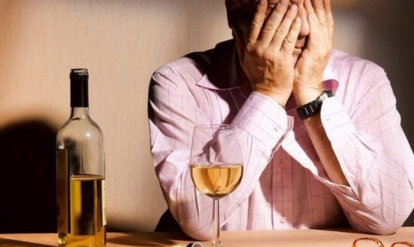 A man is sitting next to a wine bottle and glass with his hands over this face.