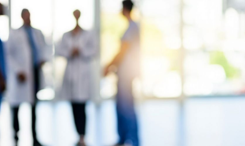 Out of focus image of a group of doctors talking.