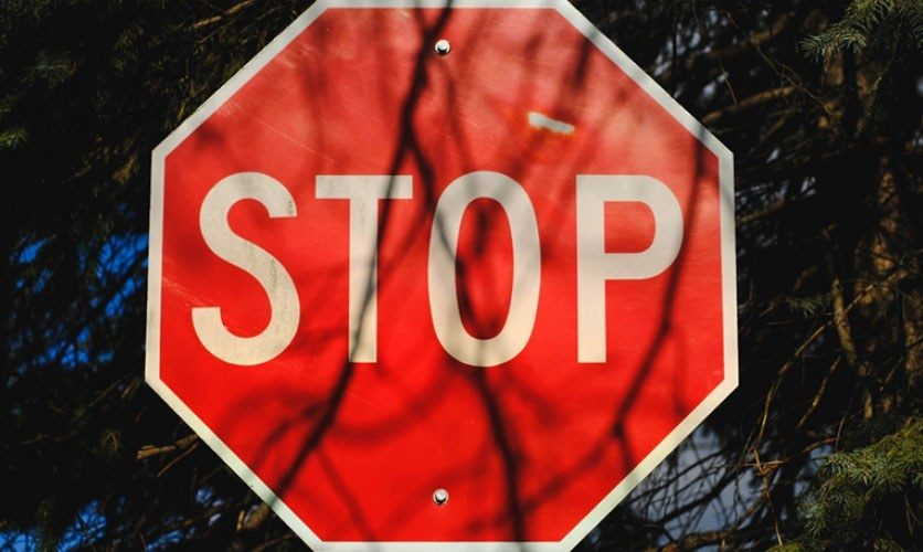 Stop sign with shadows falling across it.