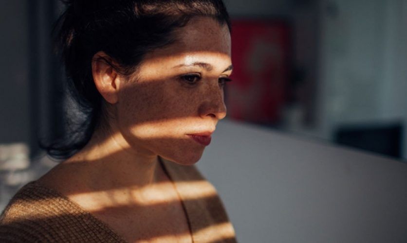 Woman in mostly shadow, with stripes of light across her face.