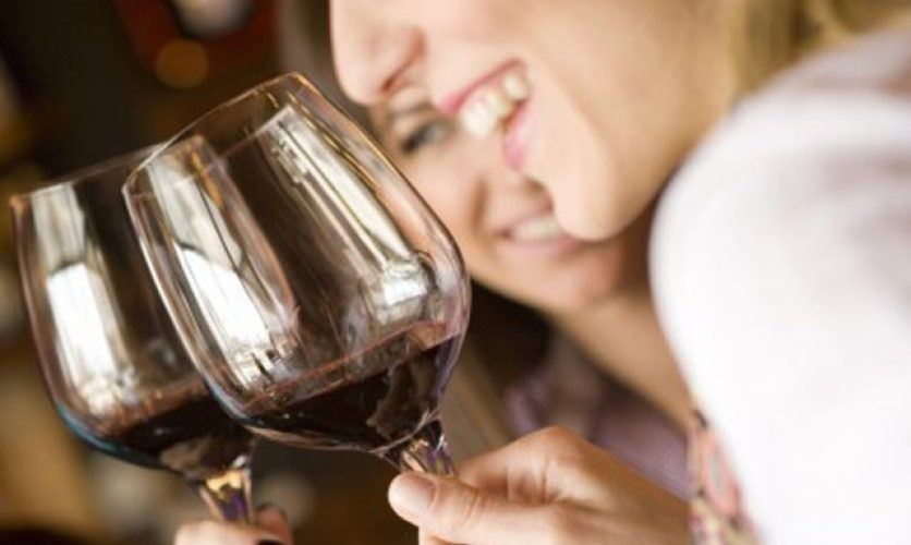 Red wine glasses in focus with two women holding them.