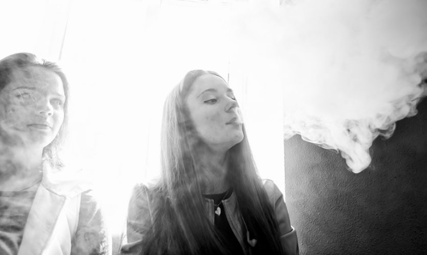 Black and white photo of young women exhaling into a cloud of smoke.